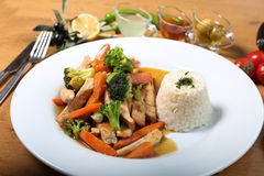 Chicken breast cuts with rice and vegetables. Ans sause on wooden table Royalty Free Stock Photography