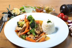 Chicken breast cuts with rice and vegetables. Ans sause on wooden table Royalty Free Stock Photo