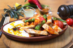 Chicken breast cuts with yogurt and vegetables. Ans sause on wooden table Royalty Free Stock Image