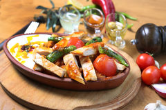 Chicken breast cuts with yogurt and vegetables. Ans sause on wooden table Royalty Free Stock Photos