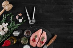 Chicken breast on a cutting board with herbs and different vegetables on rustic wooden background. Royalty Free Stock Photography