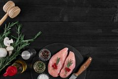 Chicken breast on a cutting board with herbs and different vegetables on rustic wooden background. Stock Image
