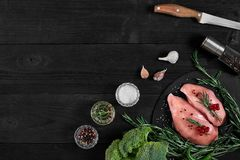 Chicken breast on a cutting board with herbs and different vegetables on rustic wooden background. Royalty Free Stock Images