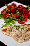 Chicken breast fillet with mushrooms. A tasty dinner dish of chicken breast fillet with mushrooms sauce, peppers, tomatoes and ruccola salad. Whole series with stock photos