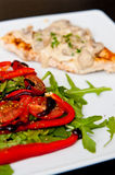 Chicken breast fillet with mushrooms. A tasty dinner dish of chicken breast fillet with mushrooms sauce, peppers, tomatoes and ruccola salad. Whole series with royalty free stock images