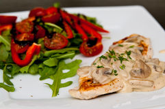 Chicken breast fillet with mushrooms. A tasty dinner dish of chicken breast fillet with mushrooms sauce, peppers, tomatoes and ruccola salad. Whole series with stock images