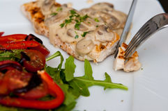Chicken breast fillet with mushrooms. A tasty dinner dish of chicken breast fillet with mushrooms sauce, peppers, tomatoes and ruccola salad. Whole series with royalty free stock photo