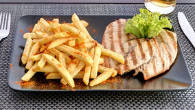 Chicken breast with french fries on black plate Stock Photos