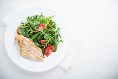Chicken breast and fresh salad with tomato and greens top view Stock Photo