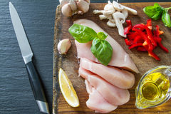 Chicken breast and ingredients on dark stone background Royalty Free Stock Photo