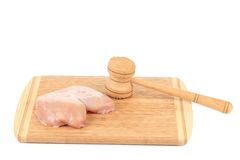 Chicken breast and meat mallet on wooden platter. Stock Photography