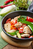Chicken breast meat and vegetables on frying pan Stock Photos