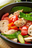 Chicken breast meat and vegetables on frying pan Royalty Free Stock Image