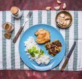 Chicken breast with mushroom sauce and rice on a blue plate with a knife and fork  wooden rustic background top view. Chicken breast with mushroom sauce and rice Royalty Free Stock Image