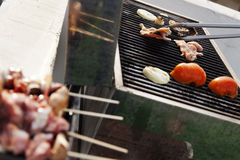 Handling the Meat. Chicken breast, onion slices, and tomatoes getting ready on an outdoor barbecue grill. tongs are handling one of the chicken breasts on the Stock Images