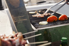 Handling the Meat. Chicken breast, onion slices, and tomatoes getting ready on an outdoor barbecue grill. tongs are handling one of the chicken breasts on the Royalty Free Stock Photo
