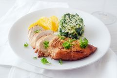 Chicken breast with orange fillets and spinach rice on a white p. Late, healthy diet dish with low calories, selective focus, narrow depth of field Royalty Free Stock Photos