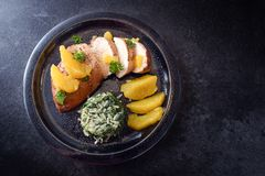 Chicken breast with orange slices and spinach rice, dark plate,. Black slate background with copy space, high angle view from above Royalty Free Stock Photo