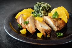 Chicken breast in orange slices with  spinach rice, healthy diet. Dinner on a dark slate background, selective focus, narrow depth of field Royalty Free Stock Photos