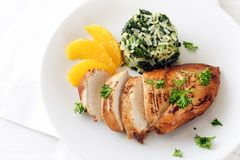 Chicken breast with orange slices and spinach rice on a white pl. Ate, top view from above, copy space, selected focus Stock Photography