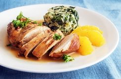 Chicken breast with orange slices and spinach rice on a white pl. Ate, diet dinner with low calories, blue tablecloth, selective focus, narrow depth of field Stock Photos