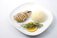 Chicken breast with rice. Grilled chicken breast with boiled rice on a white plate. Raw available stock images