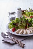 Chicken breast salad on a white plate with fork and knife Royalty Free Stock Images