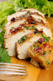 Chicken breast. Slices of roasted chicken breast on a wooden board with fresh herbs Royalty Free Stock Photography