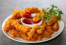 Chicken breast strips on concrete table. Delicious crispy fried breaded chicken breast strips with tomato sauce on white plate, on concrete table, view from royalty free stock image