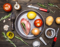 Chicken breast, tomatoes, lemon, onion, on pan rosemary, butter, potatoes, ingredients for cooking on wooden rustic background top Stock Images