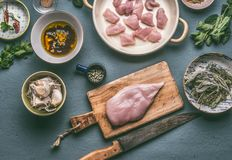 Chicken breast on wooden cutting board with knife , kitchen table background with ingredients in bowls and honey mustard marinate. Top view. Dieting cooking Stock Photo