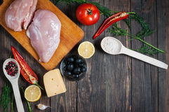 Chicken breast, wooden spoon and fresh delicious ingredients for cooking on rustic background Stock Photos