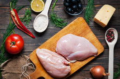 Chicken breast, wooden spoon and fresh delicious ingredients for cooking on rustic background Royalty Free Stock Photography