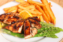 Chicken breasts with asparagus and sauce Stock Photography