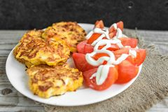 Chicken breasts coated with cheese, tomatoes on white plate, on old wooden table stock photo
