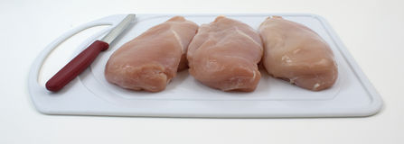 Chicken breasts on cutting board with knife Royalty Free Stock Photo