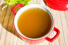 Chicken broth, bouillon, clear soup. Chicken broth, bouillon, clear soup in a cup next to fresh herbs Royalty Free Stock Images