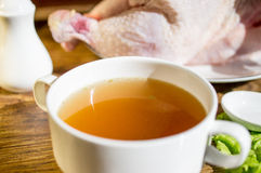 Chicken broth, bouillon, clear soup. Chicken broth, bouillon, clear soup in a cup next to chicken and fresh herbs Stock Photography