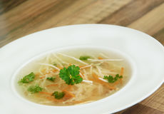 Chicken broth with carrot, celery and parsley. Closeup view of chicken bouillon on wooden background. Rich chicken bouillon with carrot, celery and parsley in a Stock Photos