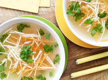 Chicken broth with carrot, celery and parsley. Top view of chicken bouillon on wooden table. Bowls of chicken bouillon with carrot, celery and parsley on wooden Stock Photo