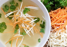 Chicken broth with carrot, celery and parsley. Top view of white bowl with chicken bouillon surrounded by ingredients. Chicken bouillon in a white bowl Stock Image
