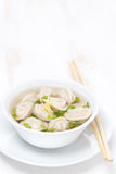 Chicken broth with Chinese dumplings on white table Royalty Free Stock Images