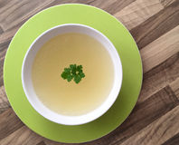 Chicken broth with green parsley. Chicken bouillon in a white plate on wooden background. Rich chicken bouillon on wooden table Royalty Free Stock Photo