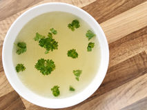 Chicken broth with green parsley. Top view of chicken bouillon on wooden table. Chicken bouillon in a white bowl on wooden background Royalty Free Stock Images