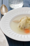 Chicken broth on white plate on blue background Royalty Free Stock Images