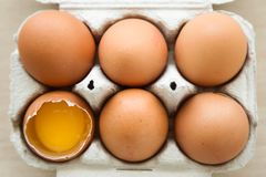 Chicken brown eggs in box, one of this eggs is half broken at home. stock image