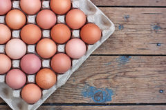 Chicken brown eggs in packing on a timber floor, the top view. F Stock Photo