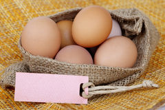 Chicken brown eggs in sack bag with blank paper tag. Stock Photography