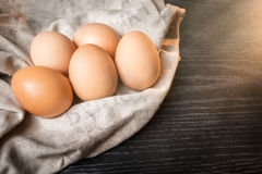 Chicken brown eggs in sackcloth on wooden backgroundChicken brown eggs in sackcloth on wooden background Royalty Free Stock Images