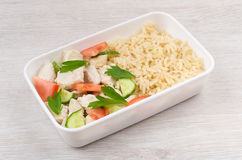 Chicken with brown rice and vegetables in plastic container Stock Images